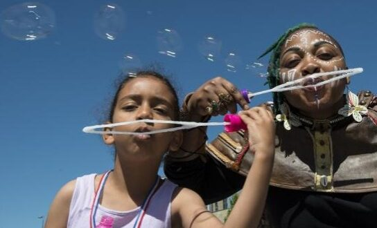 A woman with face paint and a girl in blowing bubbles together with a blue sky