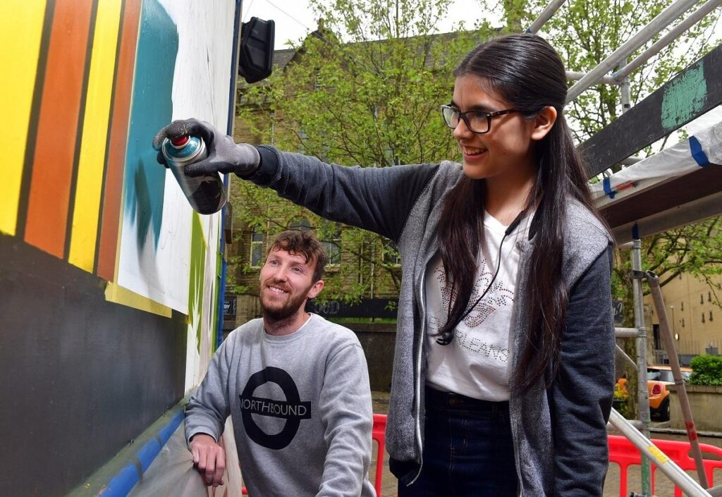 A teenage girl spray-painting a colourful design onto a wall